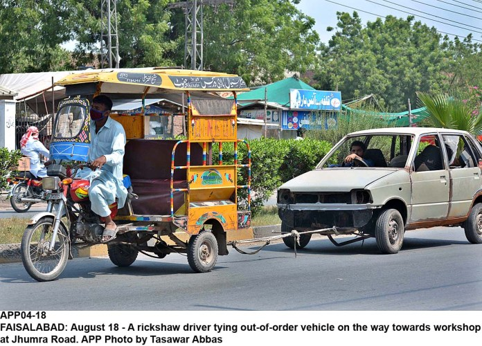 FAISALABAD: August 18 - A rickshaw driver tying out-of-order vehicle on the way towards workshop at Jhumra Road. APP Photo by Tasawar Abbas