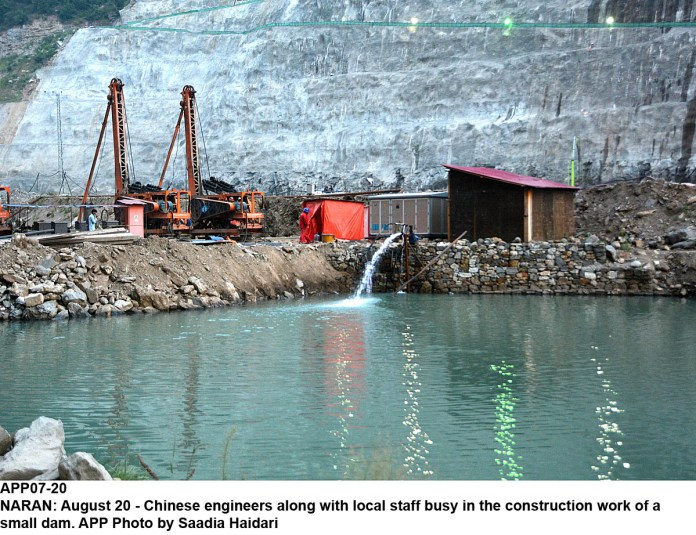 NARAN: August 20 - Chinese engineers along with local staff busy in the construction work of a small dam. APP Photo by Saadia Haidari