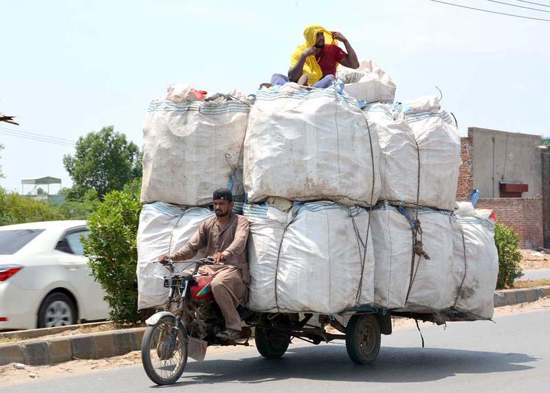 FAISALABAD: August 21 - Motorcyclist driven cart on the way overloaded with heavy stuff on City Road. APP photo by Tasawar Abbas