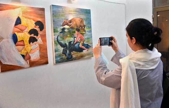 FAISALABAD: August 24 – A visitor is capturing paintings with her cell photon during three-day painting exhibition at Government College Women University Faisalabad (GCWUF). APP photo by Tasawar Abbas