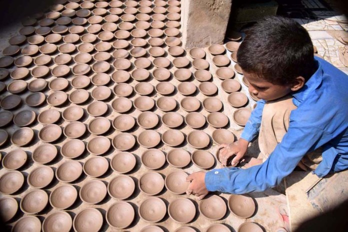 SARGODHA: August 28 – A child displays clay pots at his work place which is at high demand during Muharram to distribute charity food. APP photo by Hassan Mahmood