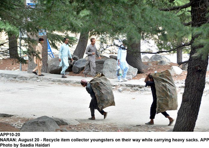 NARAN: August 20 - Recycle item collector youngsters on their way while carrying heavy sacks. APP Photo by Saadia Haidari
