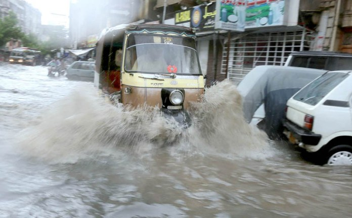 HYDERABAD: August 21 – An auto-rickshaw passing through flooded water during heavy rain in the city. APP photo by Akram Ali