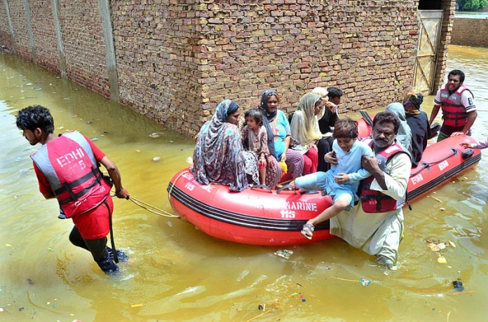 HYDERABAD: August 26 – Edhi rescue workers busy in shifting residents of Mehar Ali Shah Colony by boat to safe place in rain affected areas. APP photo by Farhan Khan