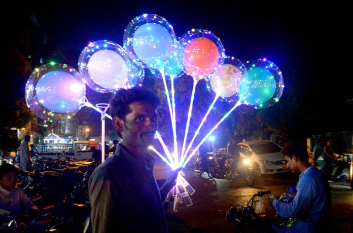 HYDERABAD: August 27 – Street vendor displaying lighting balloons to attract the customers. APP photo by Farhan Khan