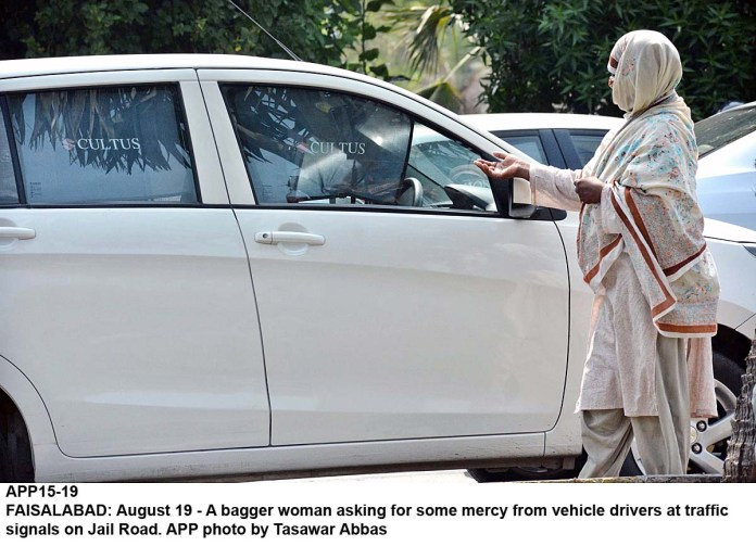 FAISALABAD: August 19 - A bagger woman asking for some mercy from vehicle drivers at traffic signals on Jail Road. APP photo by Tasawar Abbas
