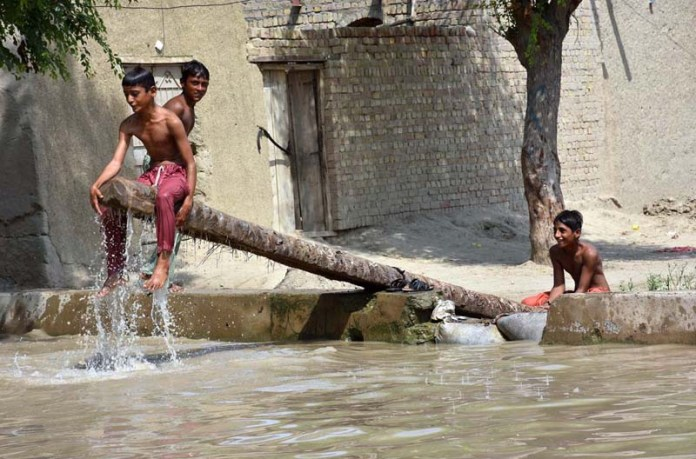 LARKANA: August 22 – Youngsters bathing in a canal to get relief from hot and humid weather. APP photo by Nadeem Akhtar