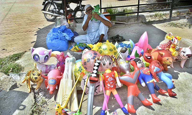 FAISALABAD: August 25 – An elderly vendor displaying plastic toys to attract the customers on footpath. APP photo by Muhammad Waseem