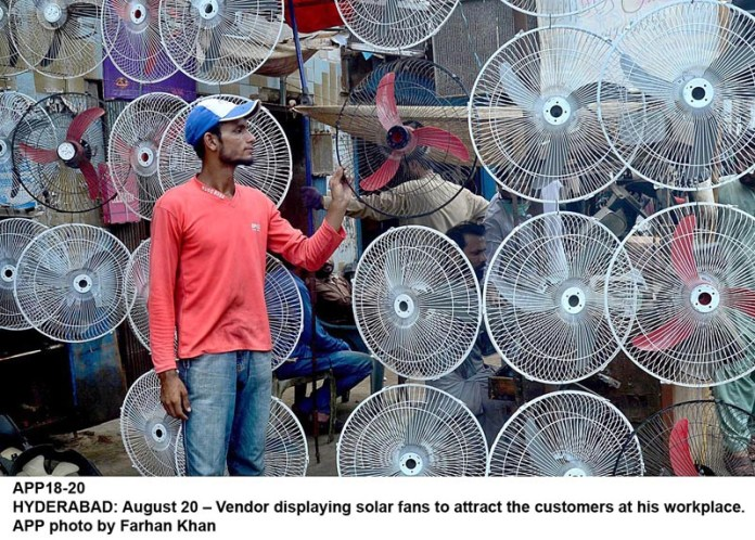 HYDERABAD: August 20 – Vendor displaying solar fans to attract the customers at his workplace. APP photo by Farhan Khan