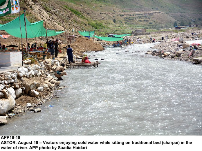 ASTOR: August 19 – Visitors enjoying cold water while sitting on traditional bed (charpai) in the water of river. APP photo by Saadia Haidari