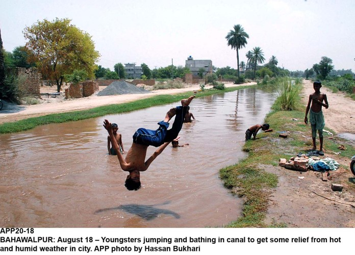 BAHAWALPUR: August 18 – Youngsters jumping and bathing in canal to get some relief from hot and humid weather in city. APP photo by Hassan Bukhari
