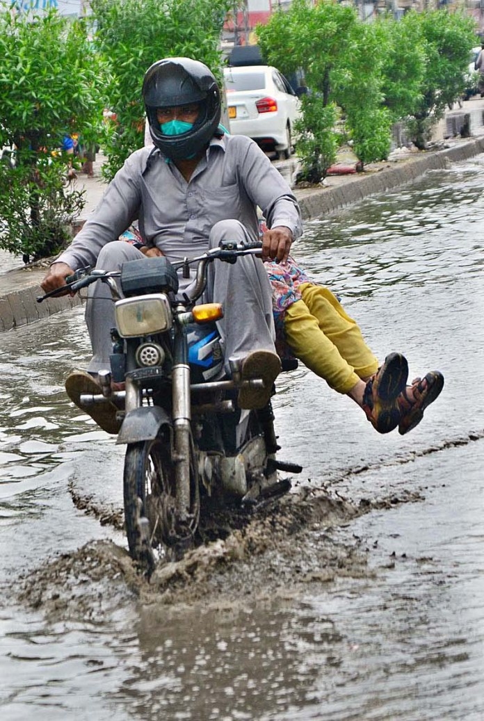 HYDERABAD: August 31 – Motorcyclist passing through rain water accumulated on the road at Latifabad after rain in the city. APP photo by Farhan Khan