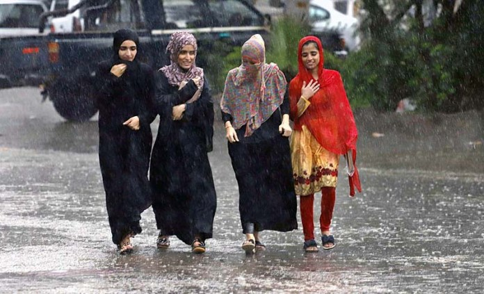 RAWALPINDI: August 31 – Girls walking on the road during rain that experienced the city. APP photo by Abid Zia
