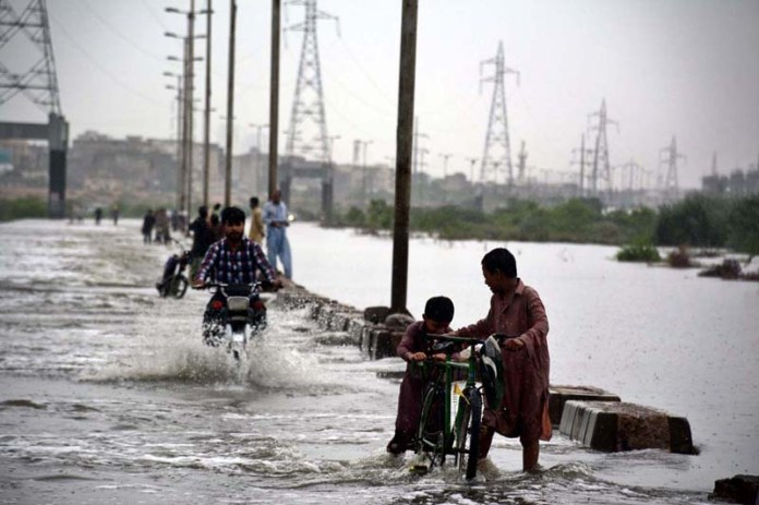 KARACHI: August 25 - Motorists crossing the flooded way towards Korangi due to overflow of Malir River after heavy rain in Provincial Capital. APP Photo by M Saeed Qureshi