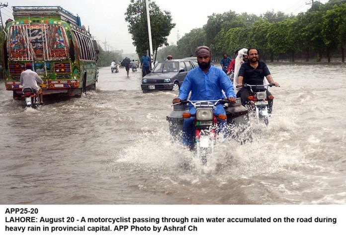 LAHORE: August 20 - A motorcyclist passing through rain water accumulated on the road during heavy rain in provincial capital. APP Photo by Ashraf Ch