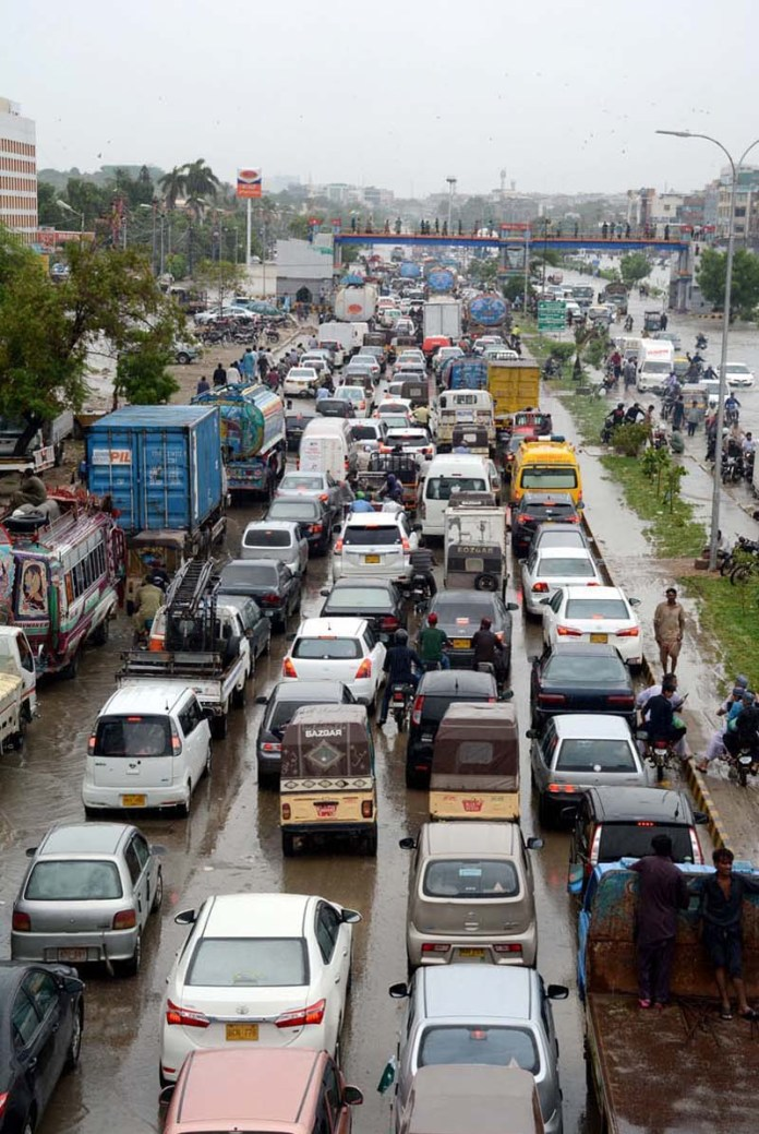 KARACHI: August 25 – A view of massive traffic due to rain water accumulated on Korangi Road after heavy rain in Provincial Capital. APP Photo by M Saeed Qureshi