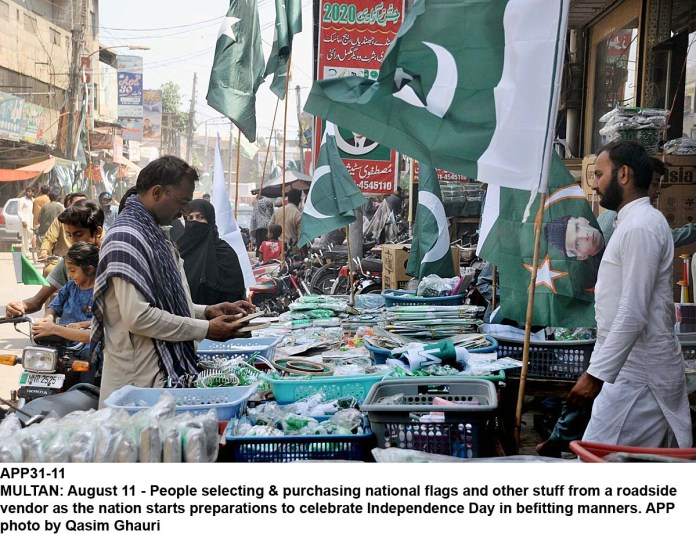 MULTAN: August 11 - People selecting & purchasing national flags and other stuff from a roadside vendor as the nation starts preparations to celebrate Independence Day in befitting manners. APP photo by Qasim Ghauri