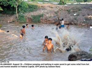 ISLAMABAD: August 16 – Children jumping and bathing in water pond to get some relief from hot and humid weather in Federal Capital. APP photo by Saleem Rana