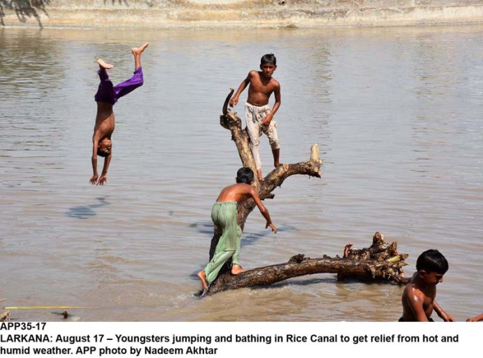 LARKANA: August 17 – Youngsters jumping and bathing in Rice Canal to get relief from hot and humid weather. APP photo by Nadeem Akhtar