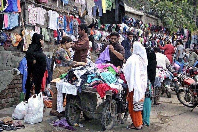 LAHORE: August 23 - Families selecting second-hand cloths from a roadside vendor in the Provincial Capital. APP photo by Rana Imran