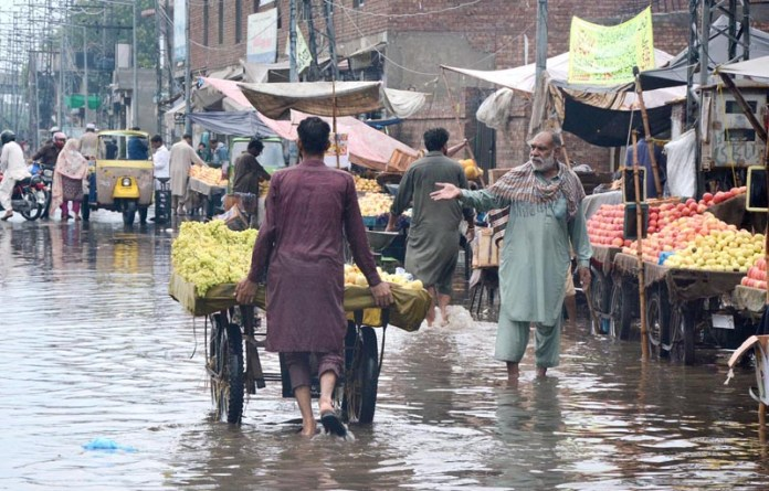 LAHORE: August 27 – Vendors wade through rain water accumulated at fruit the Provincial Capital. APP Photo by Ashraf Ch