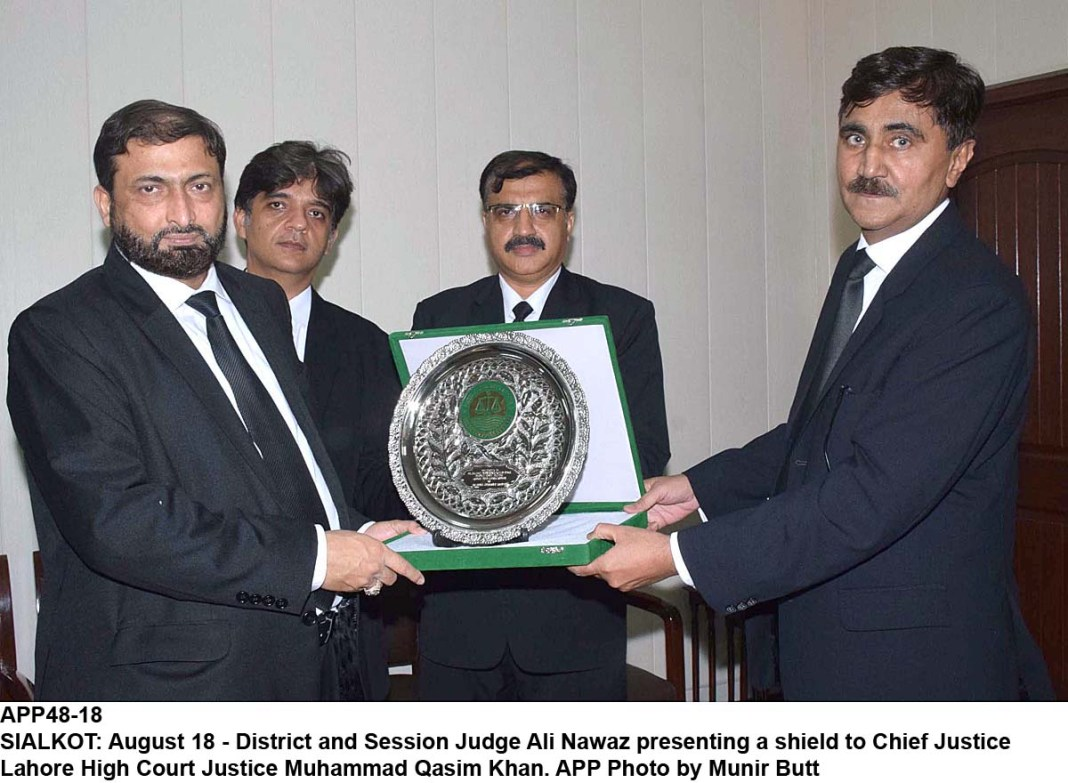 SIALKOT: August 18 - District and Session Judge Ali Nawaz presenting a shield to Chief Justice Lahore High Court Justice Muhammad Qasim Khan. APP Photo by Munir Butt