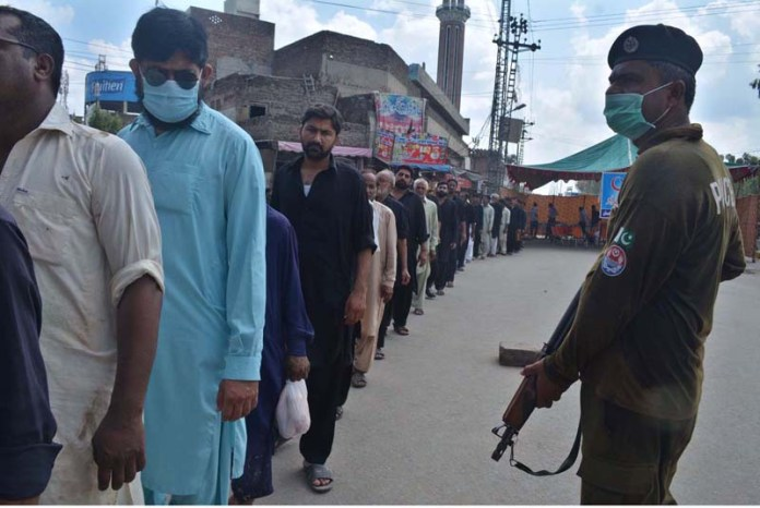SARGODHA: August 30 – A large number of devotees in queue under the guard of security personnel to attend the procession of Youm-e-Ashura, the 10th day of Muharram-ul-Harram. Ashura marks the death anniversary of Imam Hussain ibn Ali (AS), (the grandson of Prophet Mohammad (PBUH)) a 7th century revolutionary leader who was martyred in the battle of Karbala. The day of Ashura is recognised by millions across the world to remember Imam Hussain's dignified stand for social justice. APP photo by Hassan Mahmood