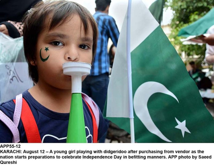 KARACHI: August 12 – A young girl playing with didgeridoo after purchasing from vendor as the nation starts preparations to celebrate Independence Day in befitting manners. APP photo by Saeed Qureshi