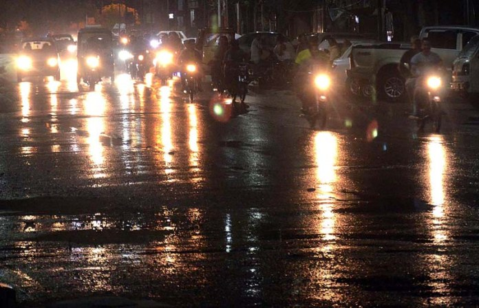 KARACHI: August 24 - A view of vehicle lights reflection on road during rain that experienced the Provincial Capital. APP photo by Syed Abbas Mehdi