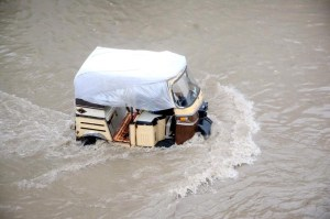 KARACHI: August 27 – An auto- rickshaw passing through flood water at Korangi area after heavy rain in Provincial Capital. APP Photo by M Saeed Qureshi