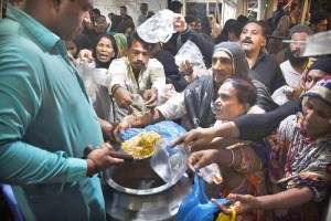 LAHORE: August 27 - A volunteer distributing free food among the devotees at Bibi Pak Daman. APP photo by Mustafa Lashari