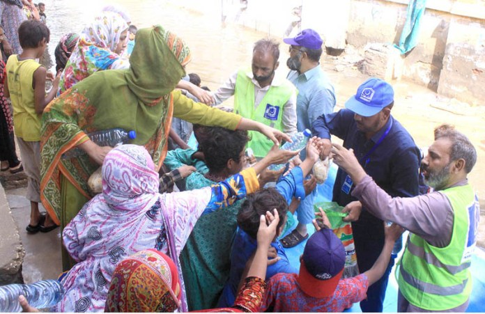 HYDERABAD: August 27 – Alkhidmat Foundation workers distribute food & water to rain affected people at Latifabad Unit Number 02 due to heavy rain in the city. APP photo by Farhan Khan