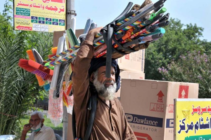ISLAMABAD; September 20 – An aged person carrying domestic use items on his head and shuttles to sell for livelihood at Aabpara market. APP photo by Saeed-ul-Mulk
