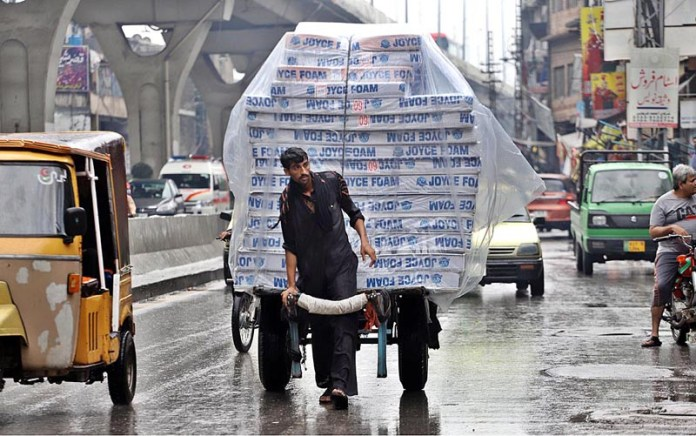 RAWALPINDI: September 01 - A labourer on the way pulling hand cart loaded with mattresses at Murree Road to deliver in a local market. APP photo by Abid Zia