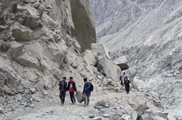 GILGIT: September 03 - People crossing Skardu-Gilgit Road blocked area by foot due to heavy land sliding at Shingus area. APP Photo by Ashraf Hussain Nasiri