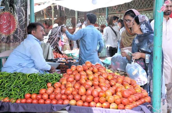 ISLAMABAD: September 27 – People purchasing vegetable from a stall at Sunday Bazar Peshawar Morr. APP photo by Saeed-ul-Mulk