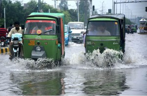 LAHORE: September 04 – Auto rickshaws passing through rain water accumulated on the road during heavy rain in provincial capital. APP photo by Ashraf Ch