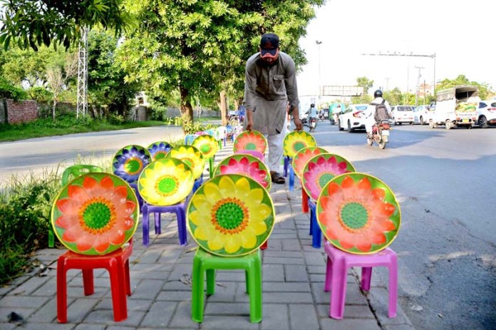 LAHORE: September 13 – Vendor busy in arranging and displaying colorful small chairs to attract the customer at his roadside setup. APP photo by Ashraf Ch