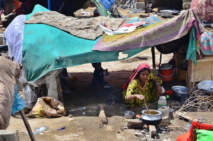 HYDERABAD: September 01 – A rain affected gypsy lady busy in cocking food while sitting in the temporary hut at Bypass area.APP photo by Farhan Khan