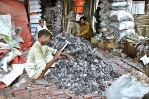 FAISALABAD: September20 – Laborers smashing black salt stones before grinding it to powder. APP photo by Muhammad Waseem
