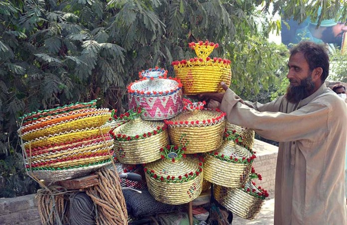 FAISALABAD: September 30 - A street vender displaying hand-made baskets at his bicycle to attract the customers. APP photo by Tasawar Abbas