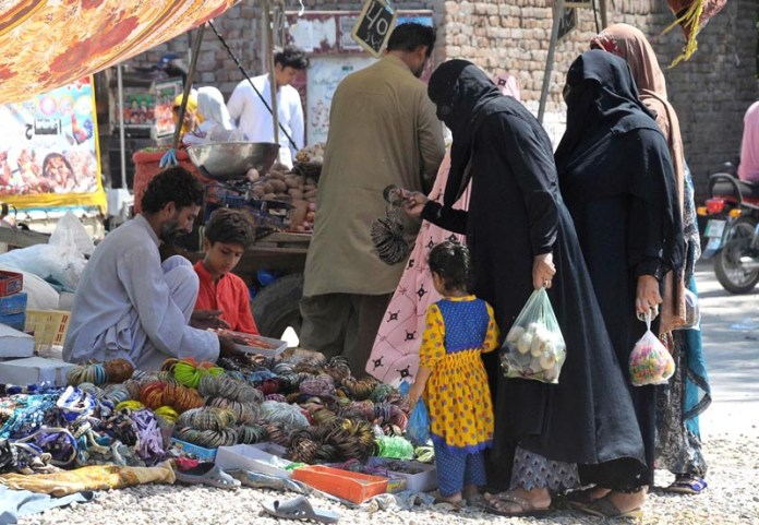 MULTAN: September 11 - Ladies selecting and purchasing bangles from a vendor at Friday Bazaar. APP photo by Qasim Ghauri