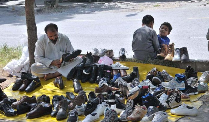 ISLAMABAD: September 19 – A vendor displays secondhand shoes to attract the customers at his roadside setup at Aabpara Market. APP photo by Saeed-ul-Mulk