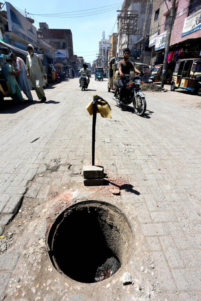 HYDERABAD: September 10 – A view of open main hole in middle of Rickshaw Market Road may cause any mishap and needs the attention of concerned authorities. APP photo by Akram Ali