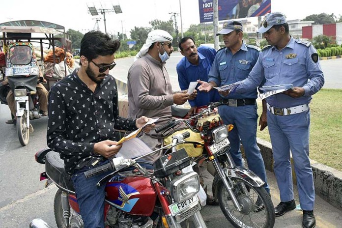 FAISALABAED: September 23 - Traffic police officials distributing pamphlets to create awareness about traffic rules and regulations. APP photo by Muhammad Waseem
