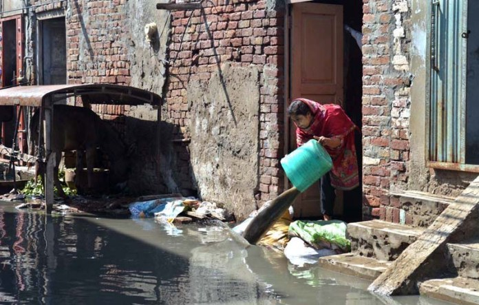 SARGDOAHA: September 01 – A woman resident of Jinnah Colony throwing the rain and sewerage water from her house. APP photo by Hassan Mahmood