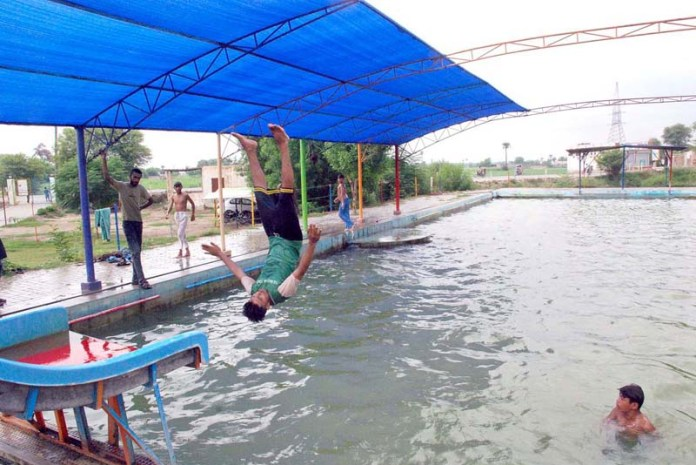 BAHAWALPUR: September 04 - People jumping in a swimming pool. APP photo by Hassan Bukhari