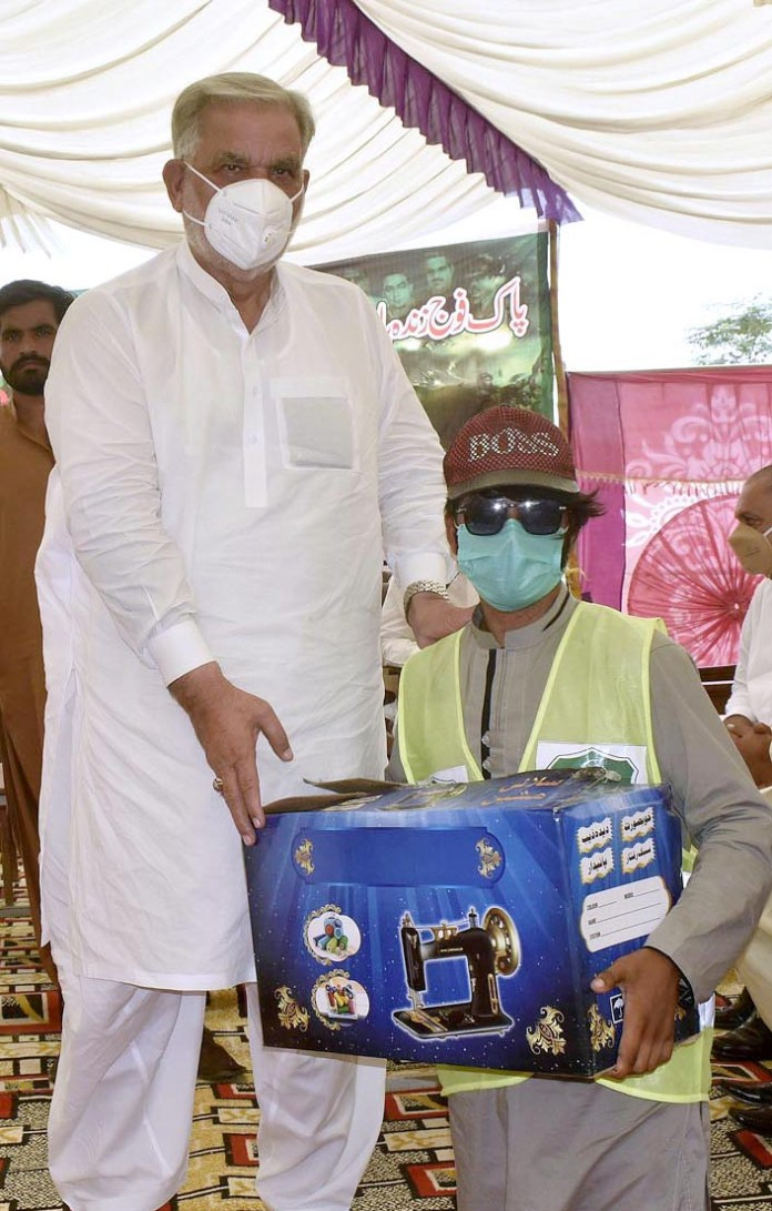 FAISALABAD: September 06 - MNA Nawab Sher Waseer distributing sewing machines among family members of martyred soldiers during a seminar on Pakistan Defense Day. APP photo by Muhammad Waseem