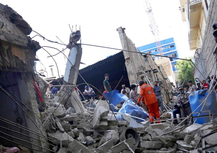 KARACHI: September 21 - Rescue operation underway after roof of Textile Factory collapsed in S I T E area in Provincial Capital. APP photo by M Saeed Qureshi
