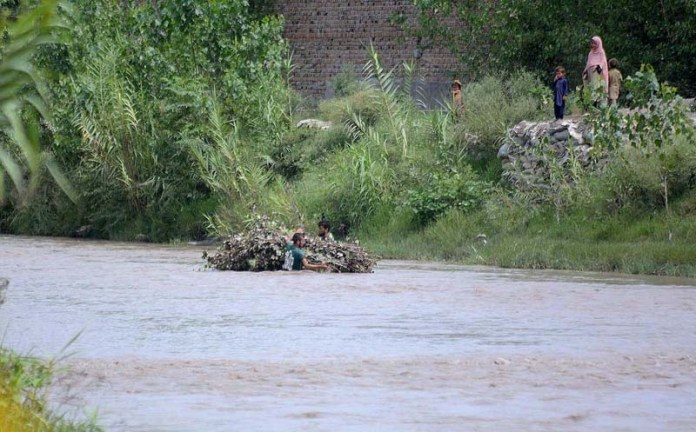 PESHAWAR: September 03 – Two persons holding tree branches while passing through flood water at Charsadda River. APP Photo by Shaheryar Anjum